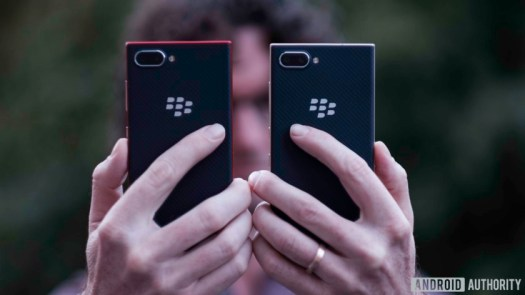 Holding two Blackberry Key2 LE devices showing backs, cameras, and BlackBerry logo
