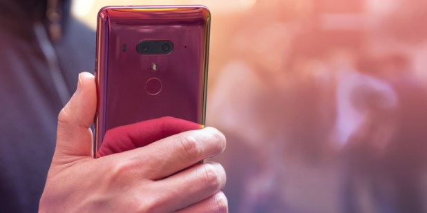 An image of a hand holding an HTC U12 Plus Flame Red edition.