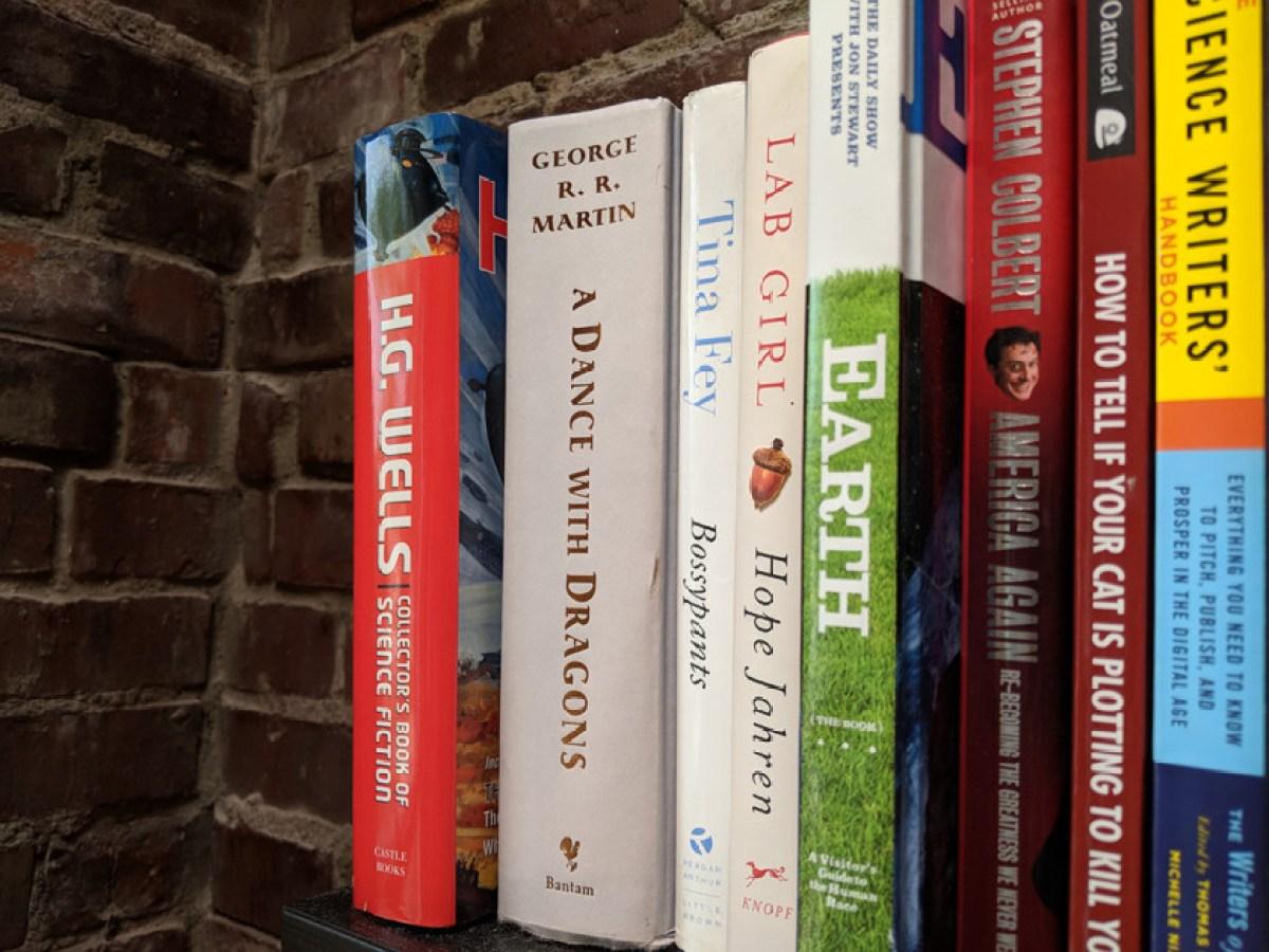 Изображение книг на полке с кирпичной стеной за ними.