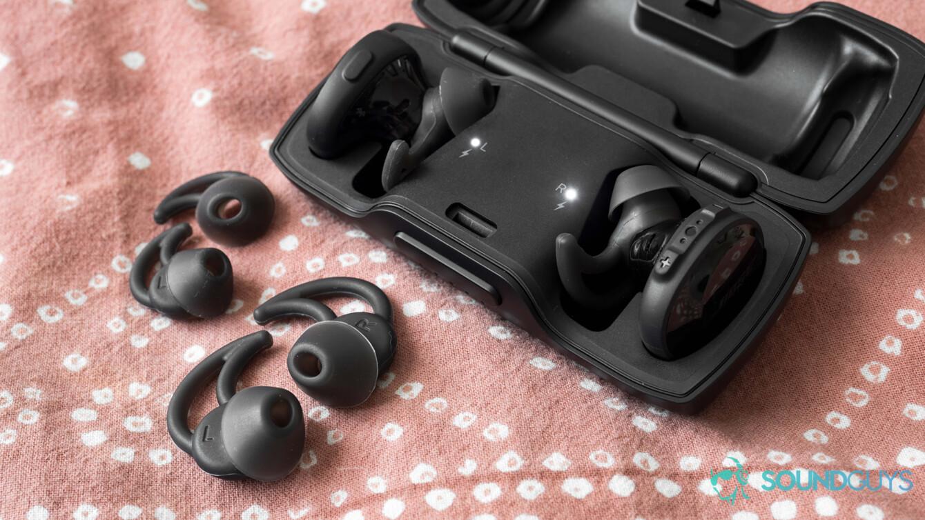 O Bose SoundSport Free no estojo com as pontas de ouvido StayHear + extras em um edredom rosa.