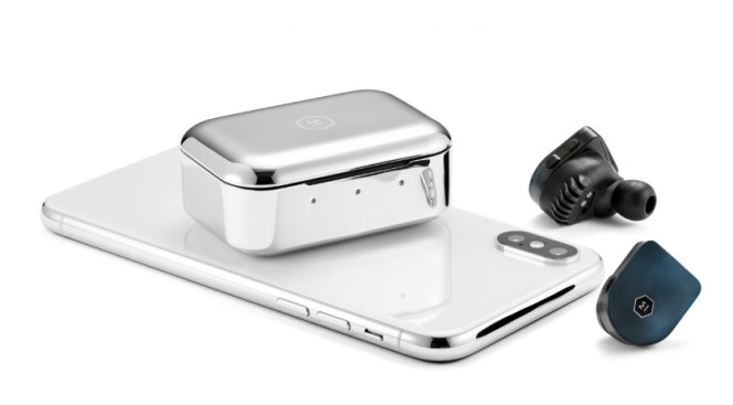 The Master & Dynamic MW07 True Wireless stainless steel charging case atop an iPhone with the steel blue earbuds on the side.