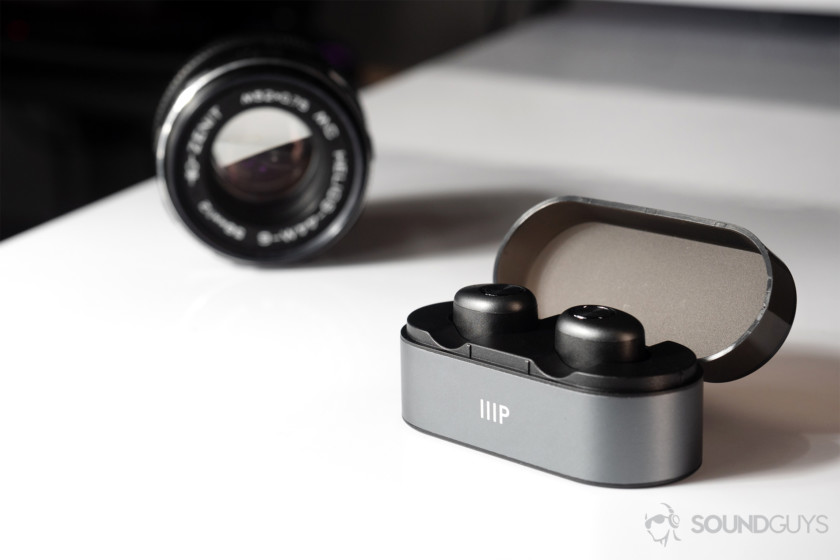 Monoprice cheap true wireless earbuds in case an din front of a black vintage lens.