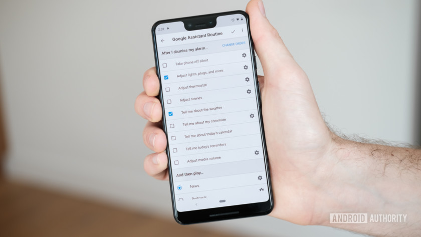 Hand holding a phone with Google Assistant routine menu pulled up.
