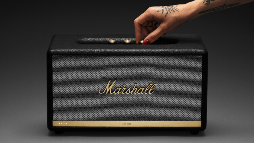 Marshall Stanmore II Voice speaker against gradient background wtih a female hand turning one of the dials.