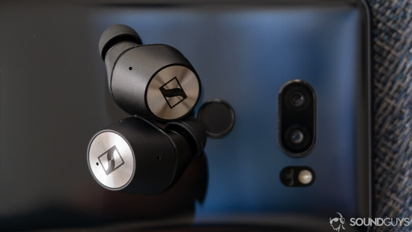 Sennheiser Momentum True wireless earbuds on a phone.