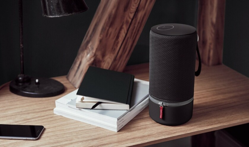 Libratone Zipp Alexa speaker in black on wood table with journals to the left.