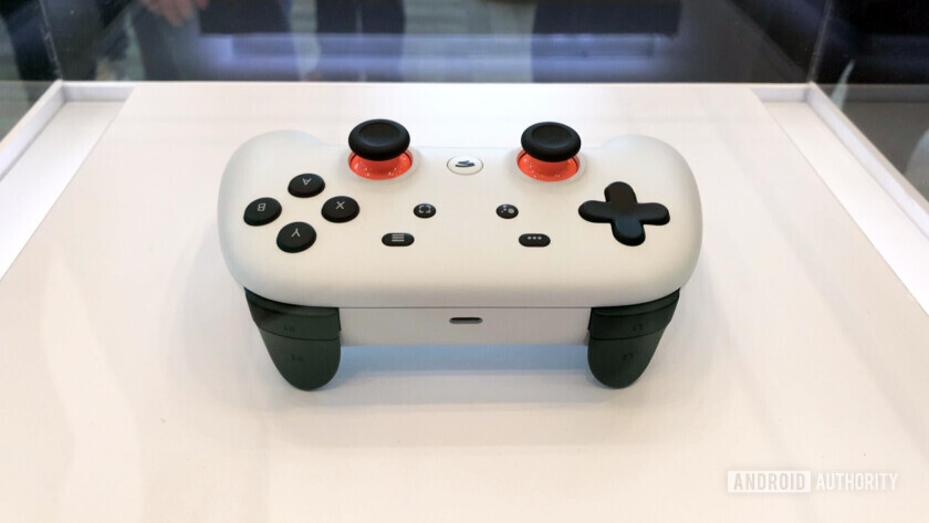 Backside view of the google stadia controller in white color in a display stand.