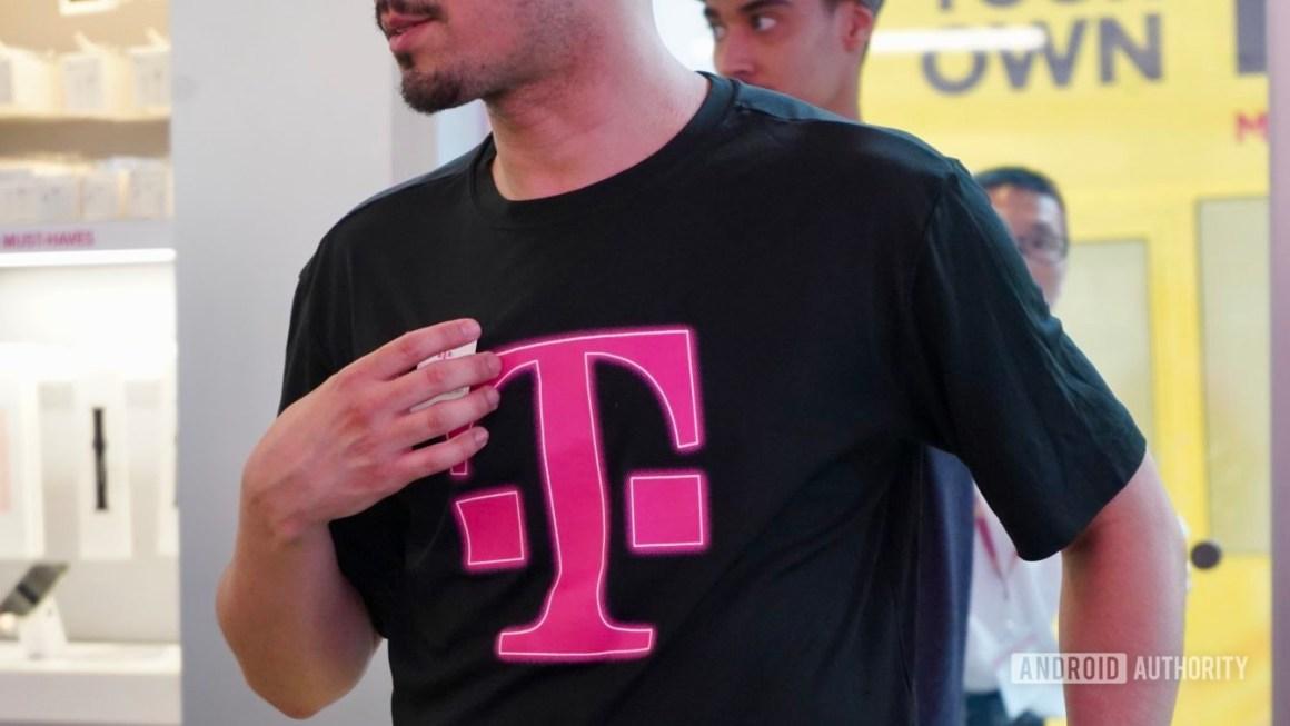 Сотрудник T-Mobile в черной футболке с логотипом T-Mobile.