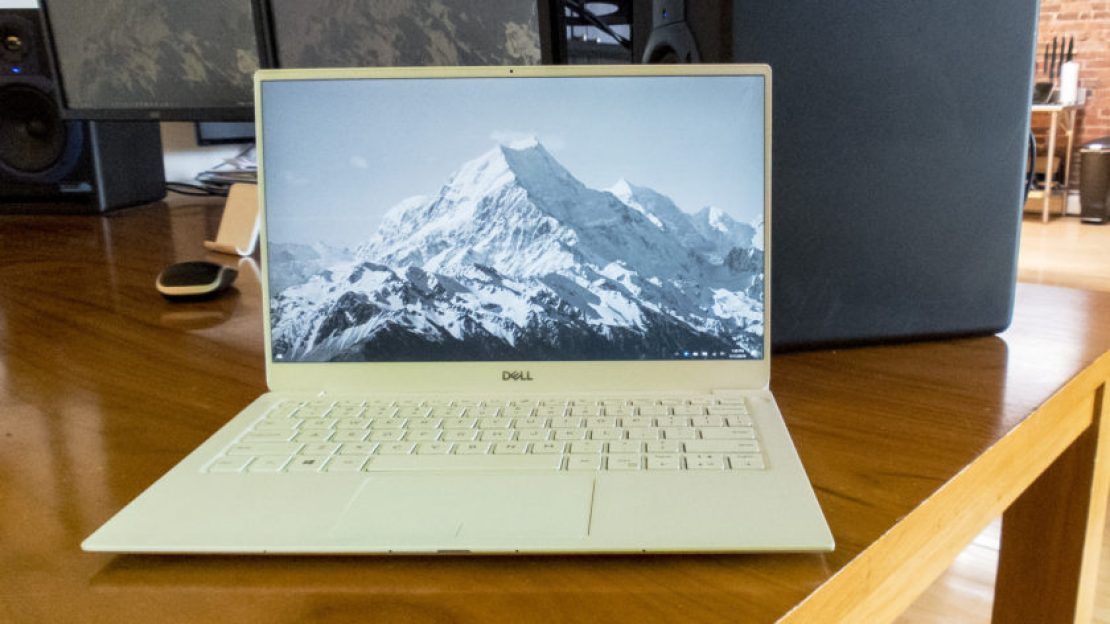 A Dell XPS 13 2019 edition sitting open on a desk with a mountain landscape photo as the background.