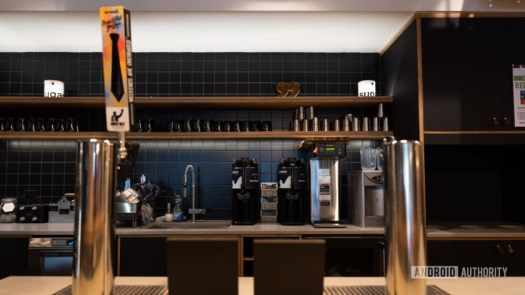 Beer taps in a WeWork with kitchen appliances in the background.