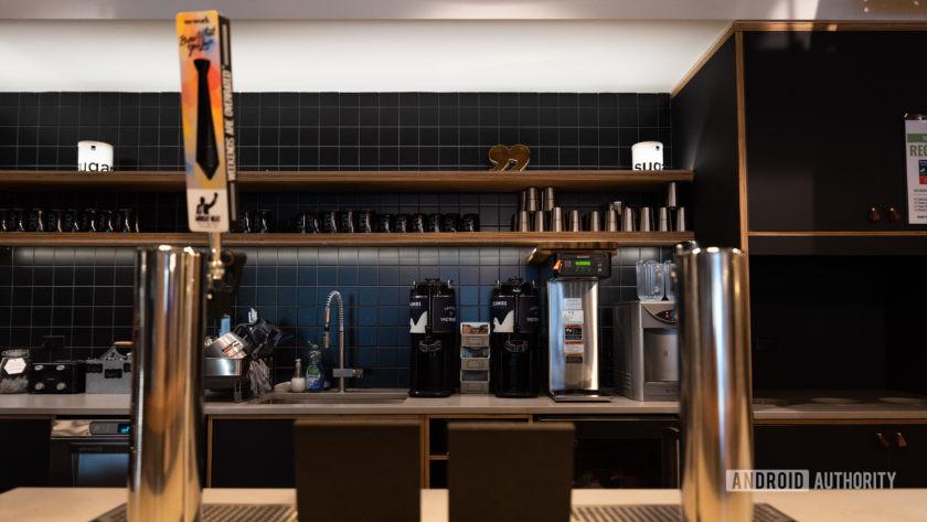 Пивные краны в WeWork с кухонными приборами на заднем плане.