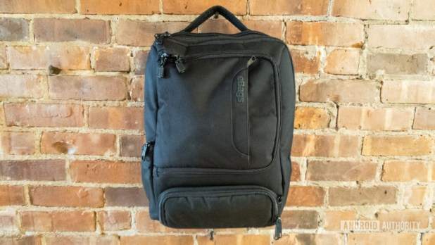 An image of the eBags Professional Slim Junior Laptop Backpack hanging on a brick wall.