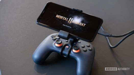 Google Stadia controller with phone mounted showing Mortal Kombat on the screen.