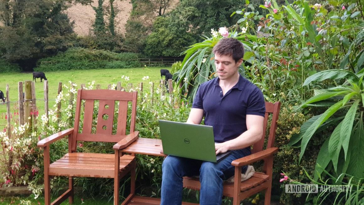 Человек в саду с привязанным ноутбуком