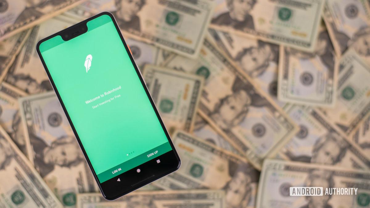 Робин Гуд приложение на смартфоне с деньгами на фоне стоковое фото