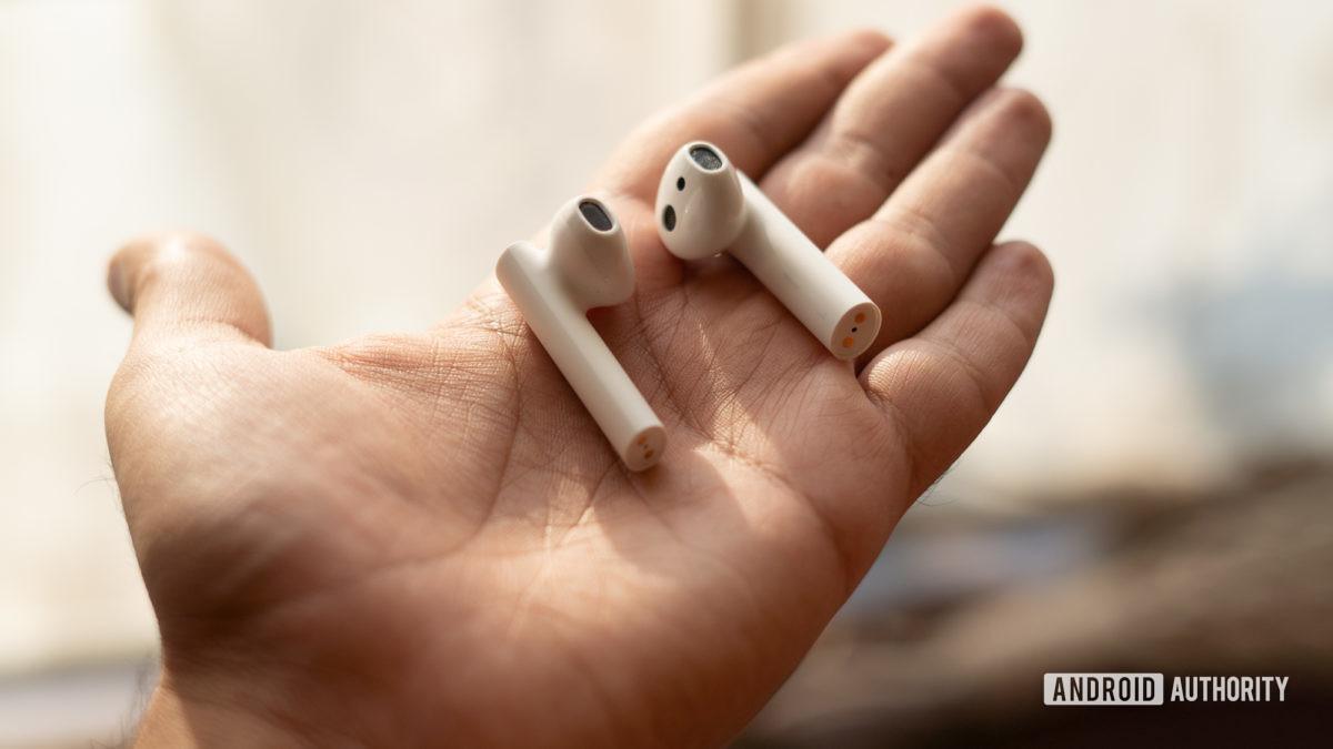 Изображение наушников Xiaomi True Wireless с 2 наушниками в руке