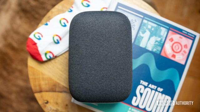 Google Nest Audio поверх кофе с книгой и парой носков Google