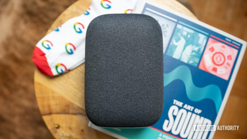 Google Nest Audio on top of coffeetable with a book and pair of Google socks