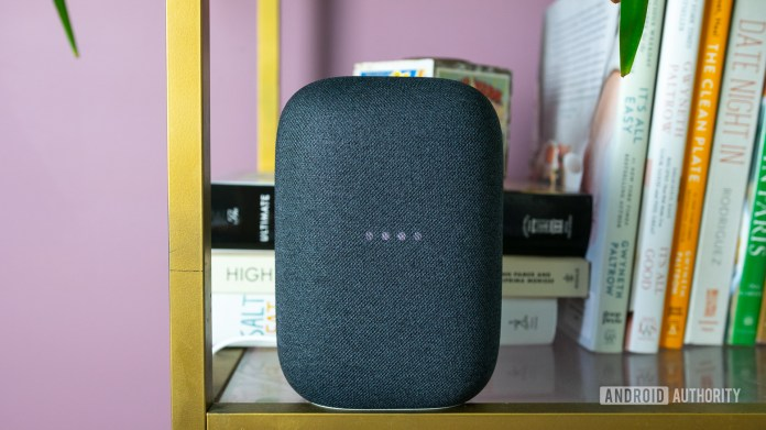 Pictured is the gray Google Nest Audio on a bookshelf with the lights blinking.