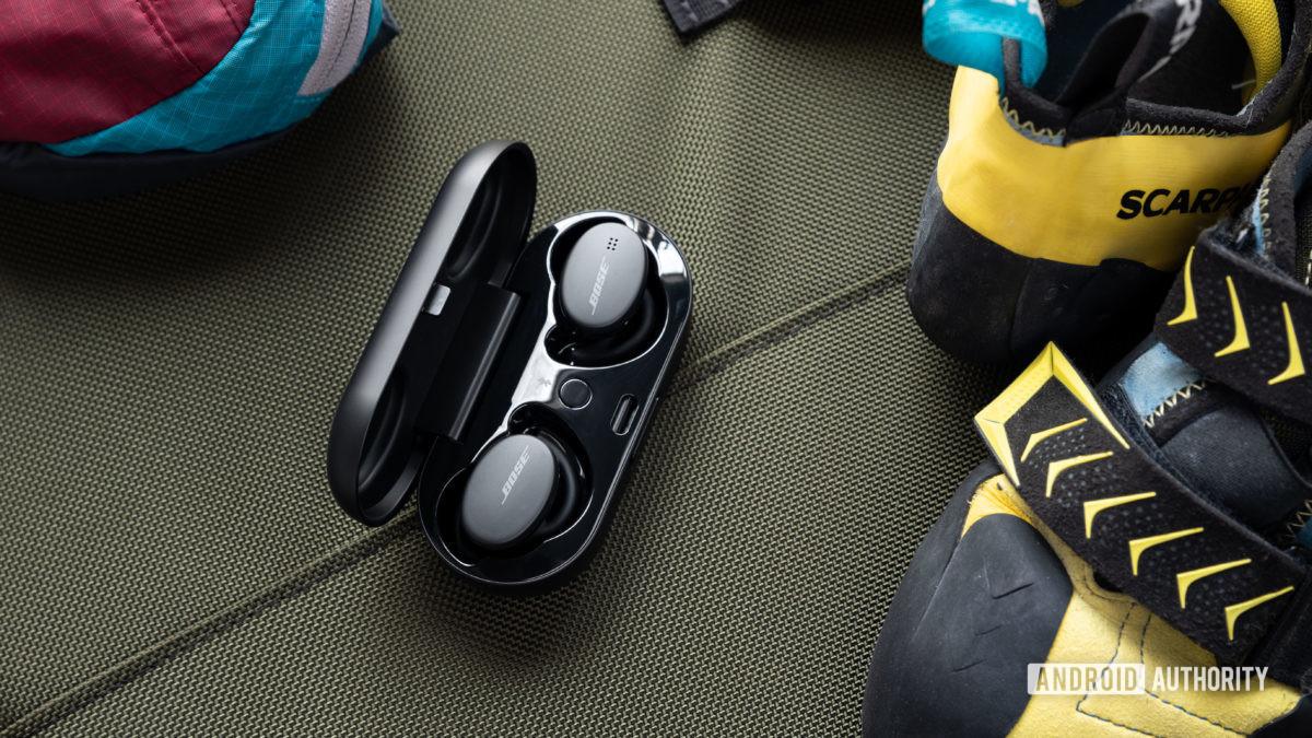 Os Bose Sport Earbuds verdadeiros fones de ouvido de treino sem fio no estojo de carregamento, ao lado de um par de sapatos amarelos de escalada.