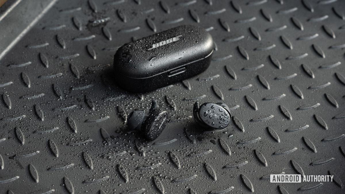 Os verdadeiros fones de ouvido de treino sem fio Bose Sport Earbuds ficam do lado de fora da caixa de carregamento fechada, todos os objetos são cobertos por respingos de água.