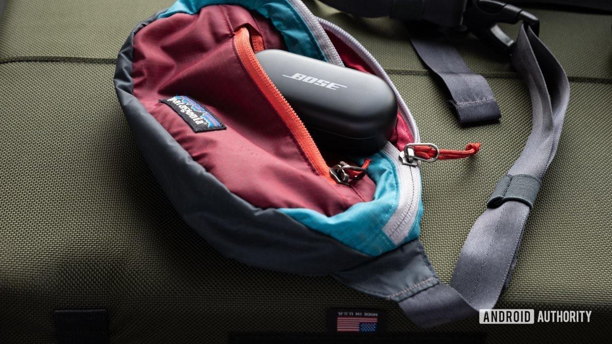 O Bose Sport Earbuds verdadeiros fones de ouvido de treino sem fio USB-C estojo de carregamento inserido pela metade em um bolso pochete.