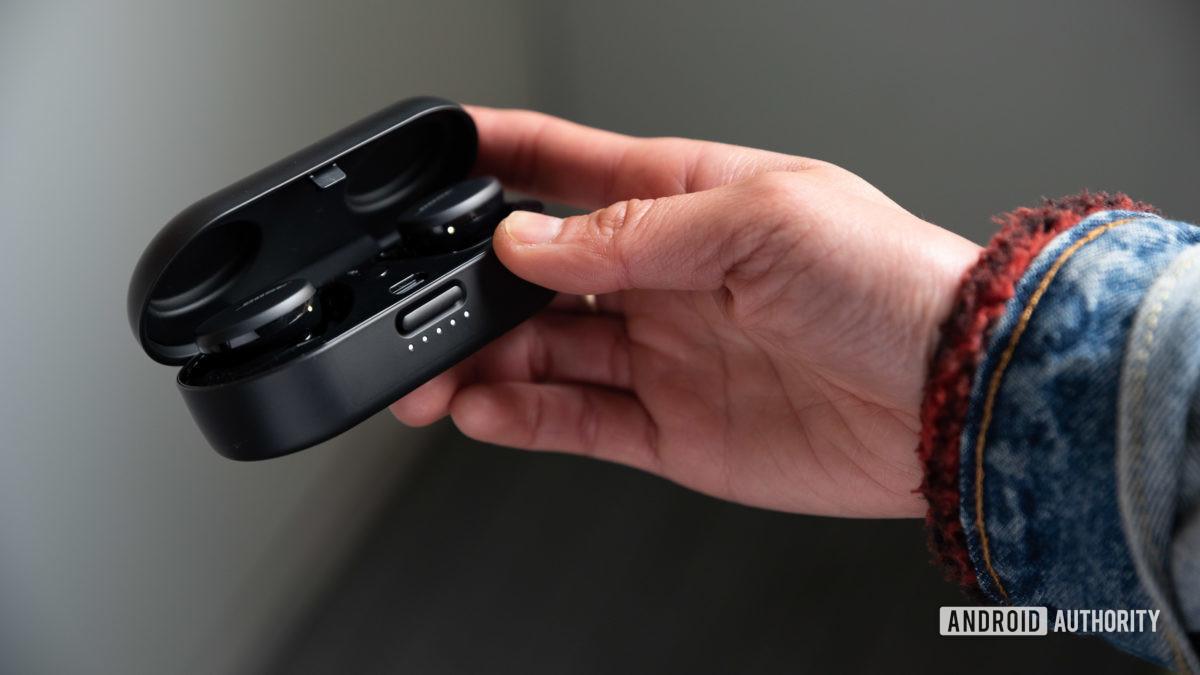 Uma mulher abre o estojo de carregamento Bose Sport Earbuds com uma mão.
