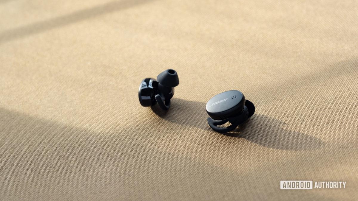 O Bose Sport Earbuds verdadeiros fones de ouvido de treino sem fio StayHear Max pontas de ouvido à vista;  os botões são contra um fundo bege.
