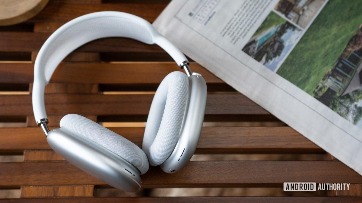 Apple AirPods Max белого цвета на решетчатой деревянной поверхности.
