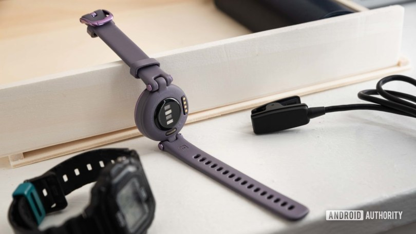 The Garmin Lily Sport Edition smart watch next to the proprietary charging cable and a Casio watch.