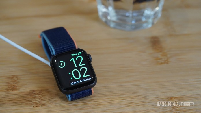 Charging Apple Watch Series 6 displays Nightstand mode on a bedside table