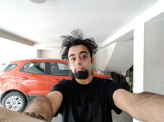 OnePlus Nord ultrawide selfie indoors of a man with black hair and a beard, wearing a black t-shirt and standing in front of a red vehicle.