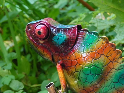 Sony Xperia 1 III camera 105mm shot of a colorful metal chameleon garden ornament in front of green leaves.