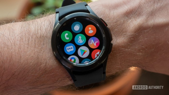 The Samsung Galaxy Watch 4 Classic on wrist showing the all apps screen containing Samsung Health, the Google Play Store, and others