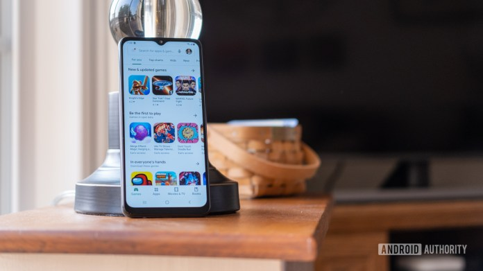 Samsung Galaxy A12 leaning against a lamp open to the Play Store