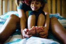 Mother Tickling Daughter' Feet Sitting Bed