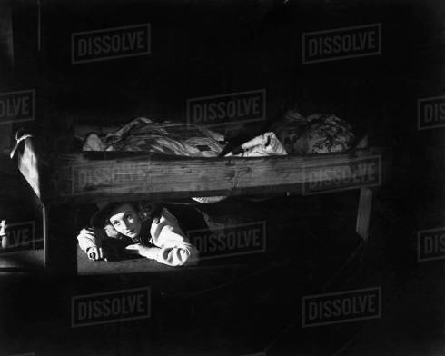 Young woman hiding under the bed - Stock Photo - Dissolve