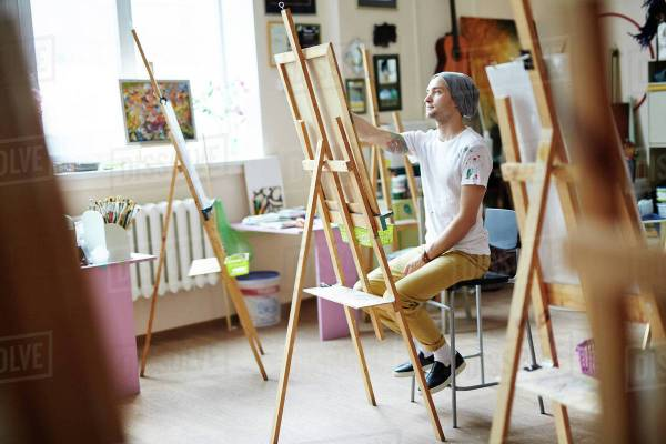 Young Male Artist In White Shirt Stained With Paint