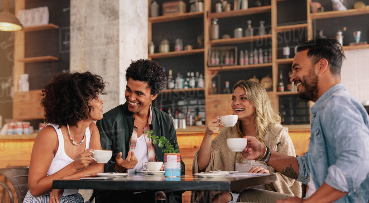 Young people sitting at a coffee shop and talking. Group of friends having coffee together in a cafe. - Stock Photo - Dissolve