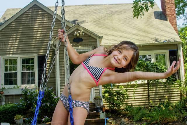 Portrait Of Girl Bending Over Sideways On Swing In Garden