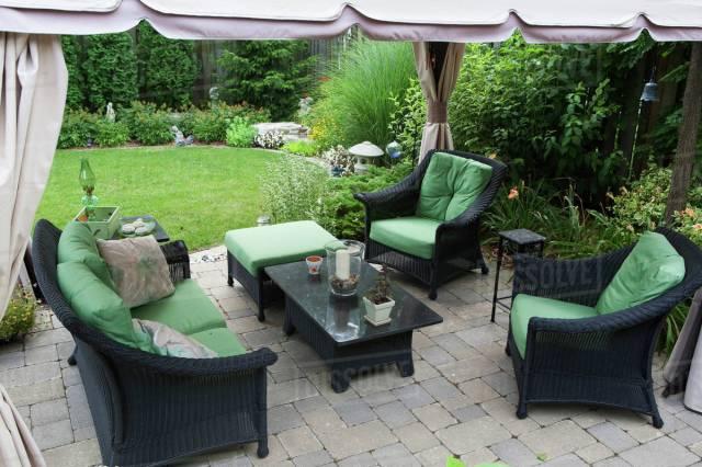 covered patio furniture on stone patio in a backyard; burlington