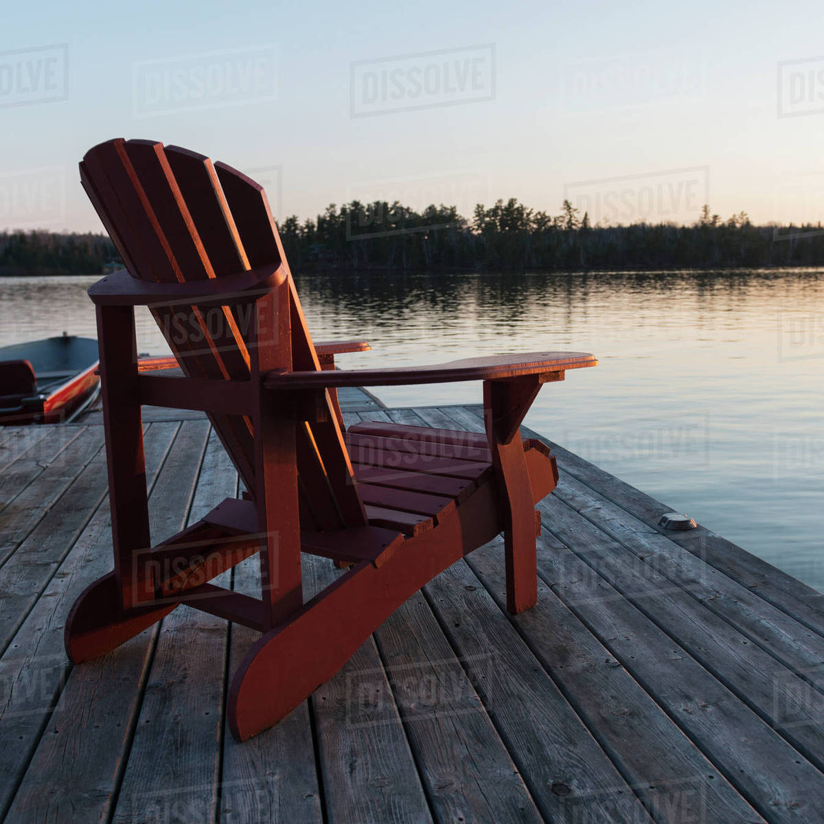 Red Adirondack Chairs A Red Adirondack Chair Sitting On A Wooden Dock On A Lake At Sunset Lake Of The Woods Ontario Canada Stock Photo
