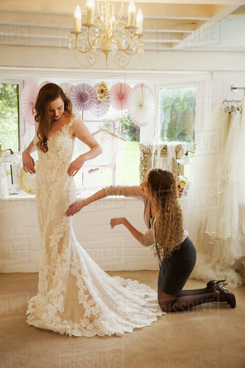 A dressmaker taking in a wedding dress, pinning and