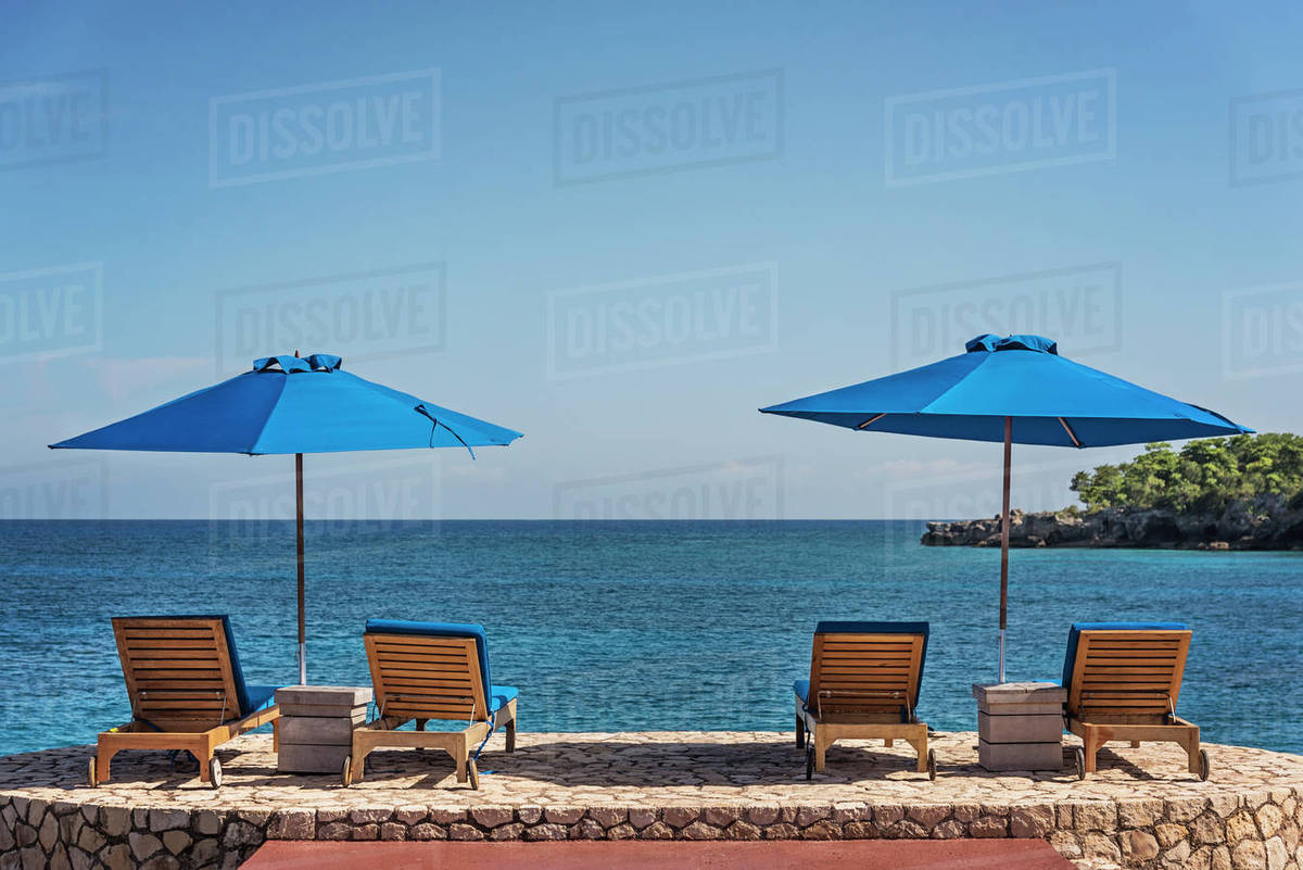 Beach Chairs With Umbrella Jamaica Negril Beach Umbrellas And Lounge Chairs Against Tranquil Seascape Stock Photo