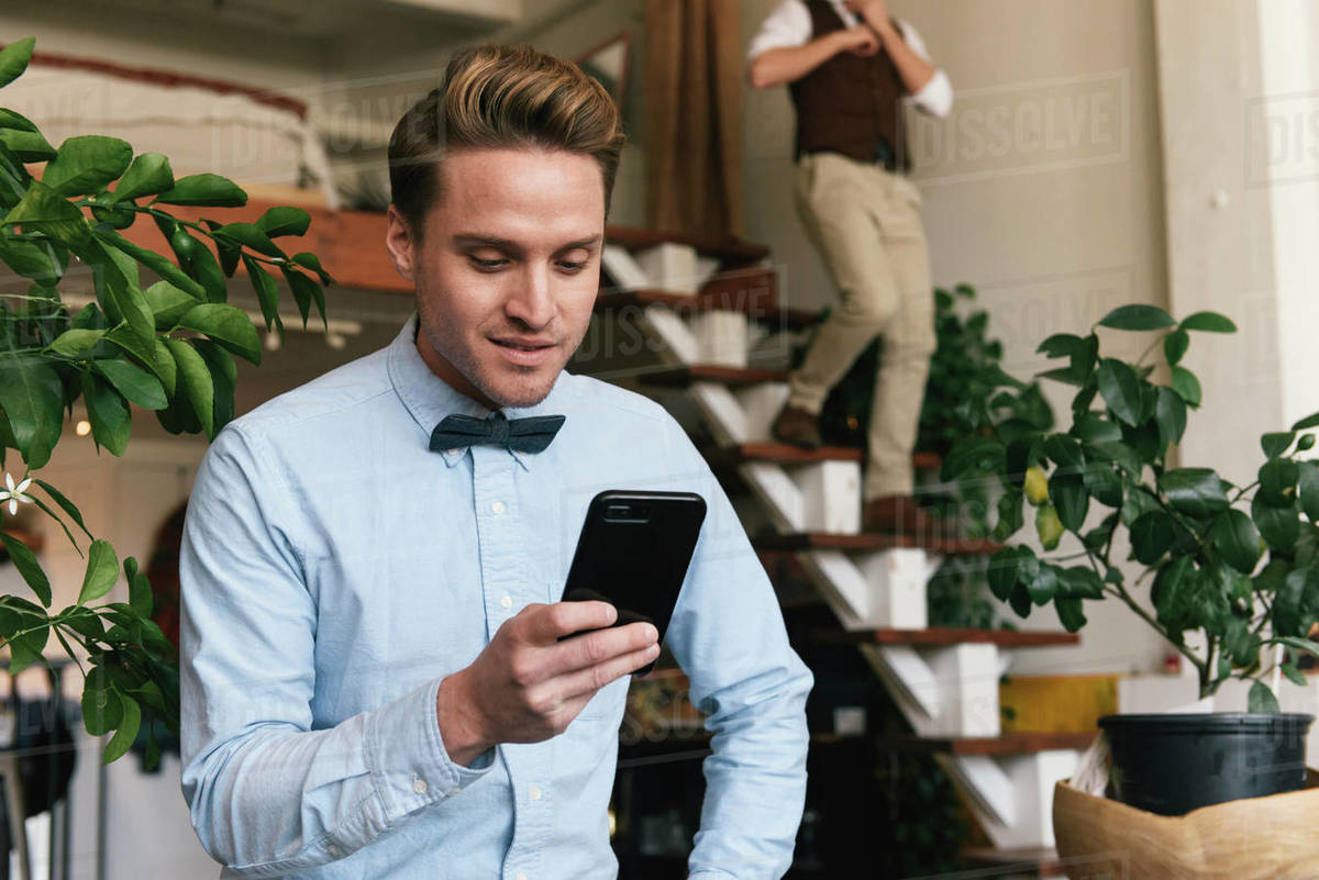 Gay Man Using Smart Phone While Boyfriend Walking Down Steps In Background At Home