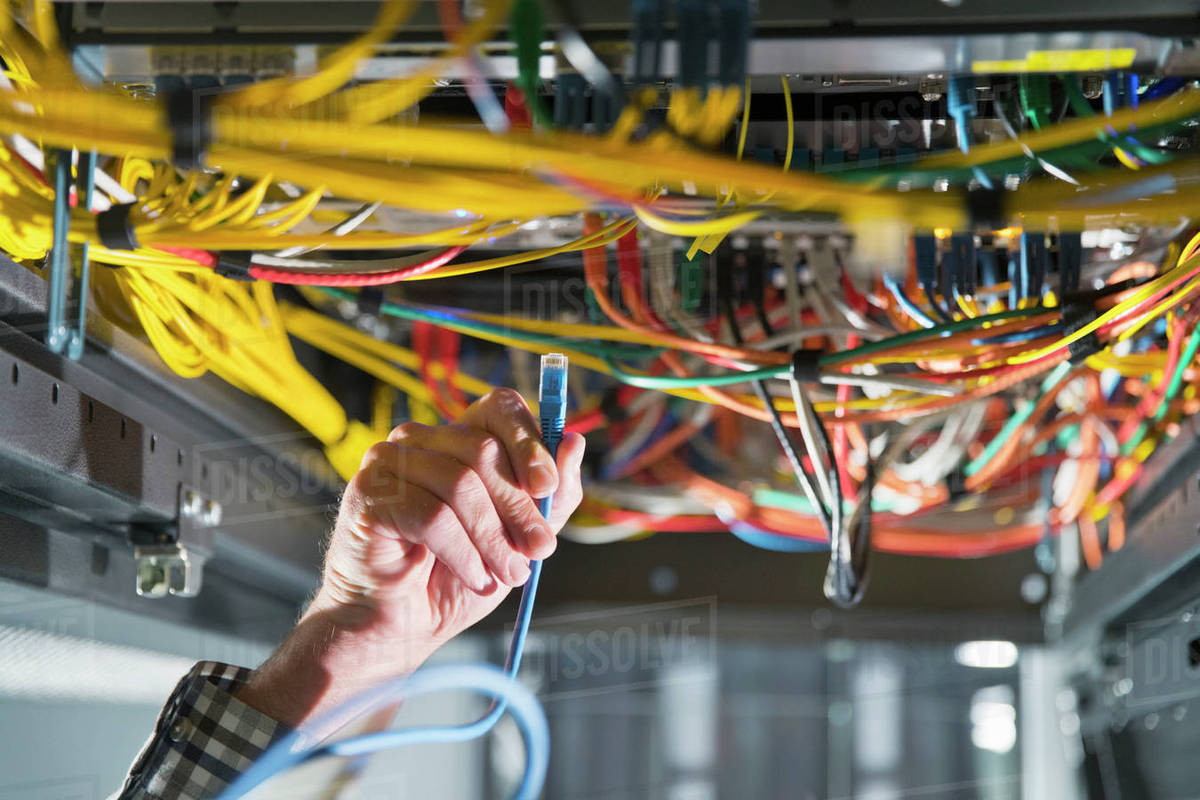 hight resolution of technician in secure data centre inspecting server wiring