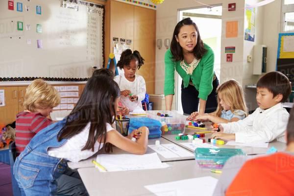 Teacher Teaching Elementary Kids With Block Play In Class
