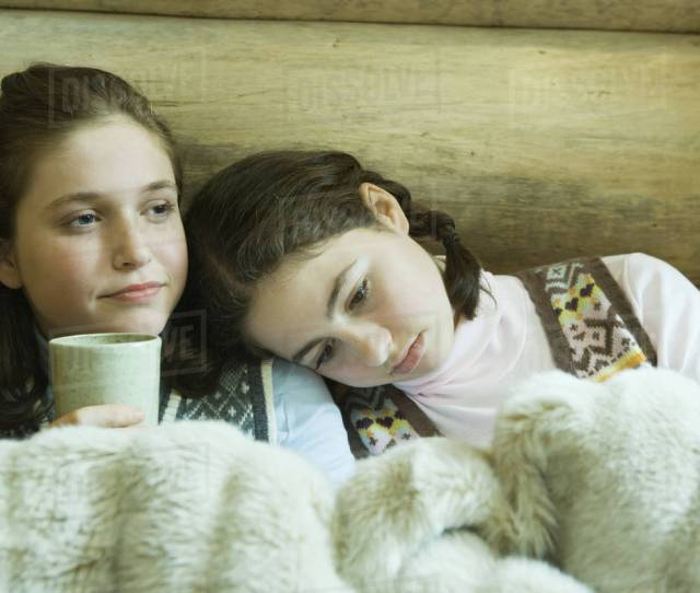 Two Teen Girls In Winter Clothes Sitting Under Warm Blanket Together One Holding Hot Beverage