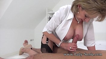 Mature British blonde with big tits jerks off a hard cock