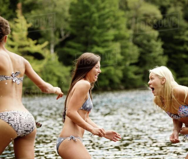 Teen Girls 16 17 With Young Woman Playing By Lake Wearing Bikinis